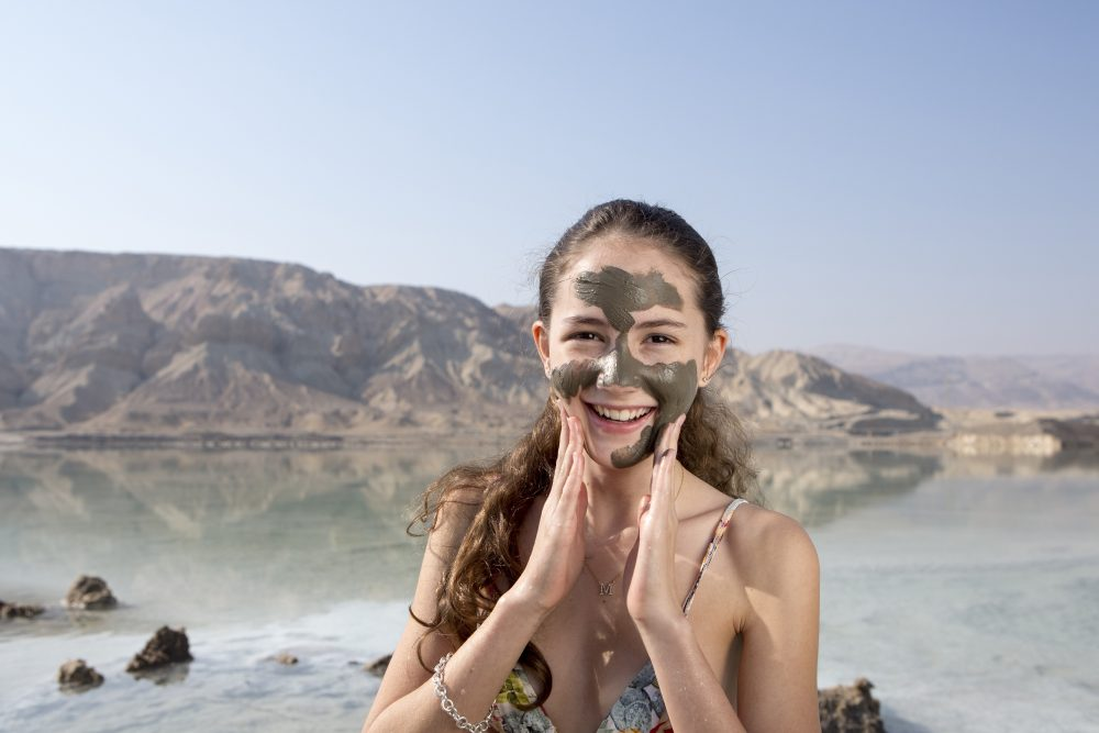 Girl using healing mineral mud at the Dead Sea in Israel