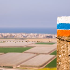 Colorful Israel Trail route sign pole barbed wire.